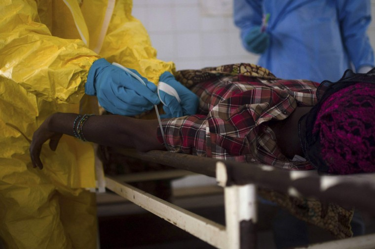 Medical staff take a blood sample from a suspected Ebola patient at the government hospital in Kenema, July 10, 2014. Ebola has killed 632 people across Guinea, Liberia and Sierra Leone since an outbreak began in February, putting strain on a string of weak health systems facing one of the world's deadliest diseases despite waves of international help. Picture taken July10, 2014. (Tommy Trenchard/Reuters)