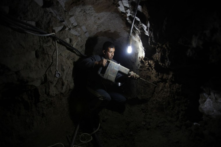 A Palestinian worker repairs a smuggling tunnel flooded by Egyptian forces, beneath the Egyptian-Gaza border in Rafah, in the southern Gaza Strip on February 10, 2013. (REUTERS/Ibraheem Abu Mustafa)