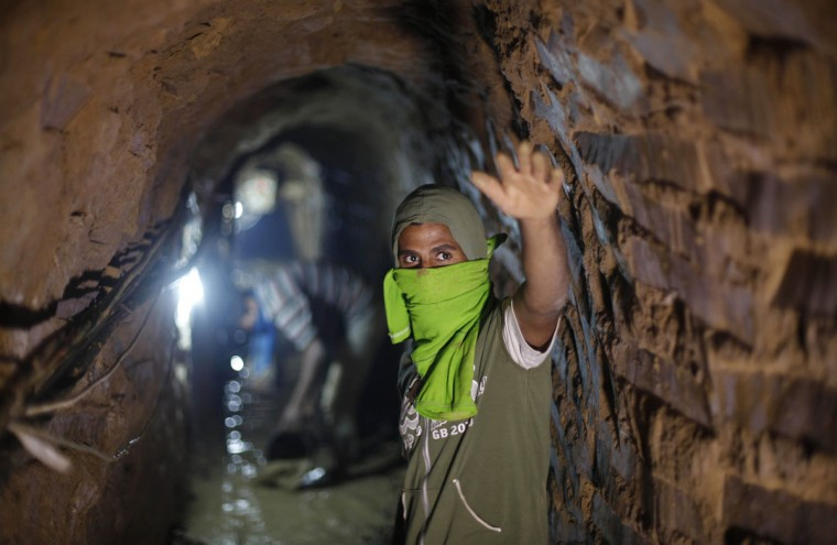 A Palestinian tunnel worker gestures as he repairs a smuggling tunnel flooded by Egyptian security forces, beneath the Gaza-Egypt border in the southern Gaza Strip on September 10, 2013. (REUTERS/Ibraheem Abu Mustafa)