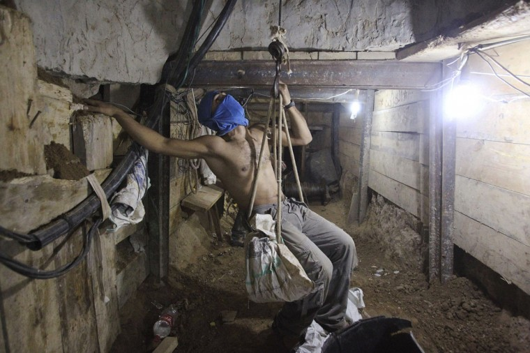 A tunnel worker ascends on a rope inside a smuggling tunnel dug beneath the Gaza-Egypt border in the southern Gaza Strip on October 8, 2013. (REUTERS/Ahmed Zakot)