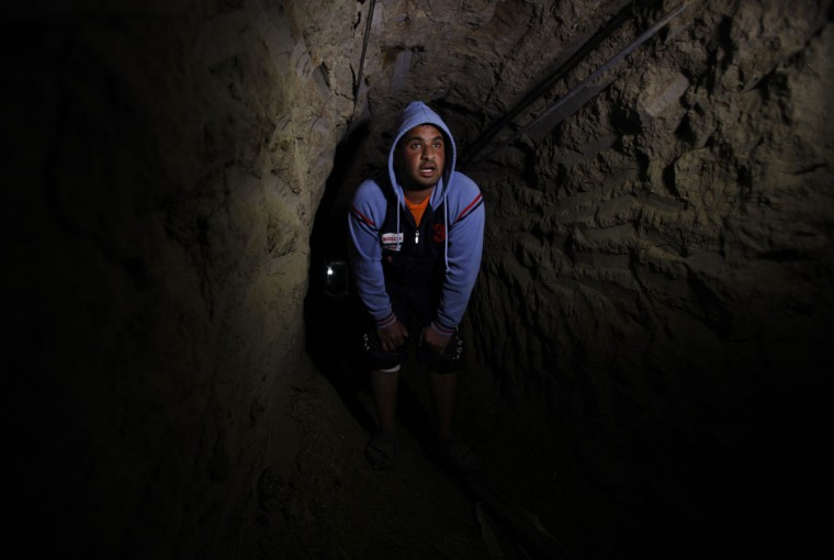 A Palestinian works inside a smuggling tunnel flooded by Egyptian forces, beneath the Egyptian-Gaza border in Rafah, in the southern Gaza Strip on February 10, 2013. (REUTERS/Ibraheem Abu Mustafa)