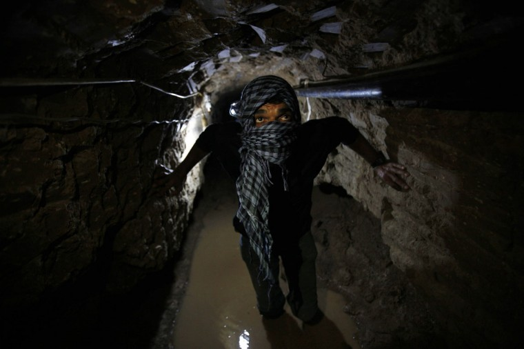 A Palestinian works inside a smuggling tunnel flooded by Egyptian forces, beneath the Egyptian-Gaza border in Rafah, in the southern Gaza Strip on February 19, 2013. (REUTERS/Ibraheem Abu Mustafa)