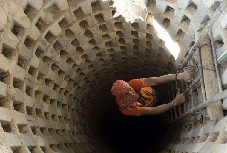 A Palestinian smuggler climbs down into a tunnel, temporarily closed by Hamas forces, beneath the Egyptian-Gaza border in Rafah in the southern Gaza Strip on April 14, 2010. (REUTERS/Ibraheem Abu Mustafa)