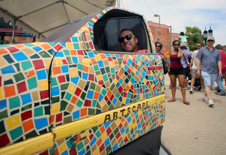 Zach Pekor, Baltimore, smiles as he has his picture taken while sitting in a mini art car on display in the Art Cars area of Artscape 2014. (Al Drago/Baltimore Sun)