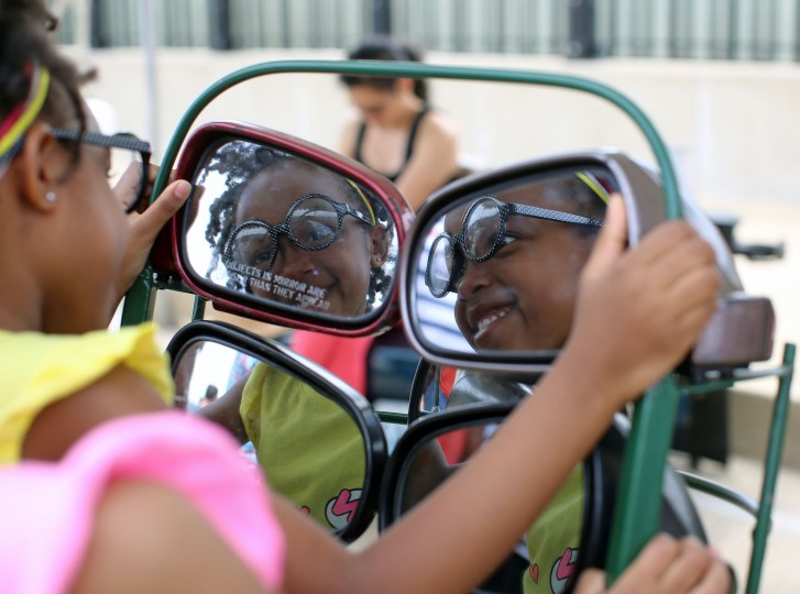 Abagail Smith, 4, Catonsville, smiles at her reflection in a chair made of rear view mirrors at Artscape 2014. Abigail is used to dual images as she has a twin sister, Audrey, who stood beside her. (Al Drago/Baltimore Sun)