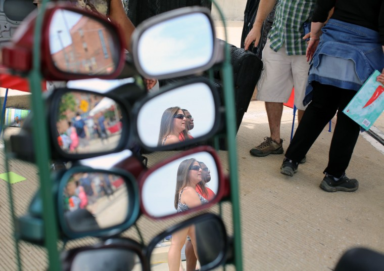 People are reflected as they walk past a chair made from car rear view mirrors at Artscape 2014. (Al Drago/Baltimore Sun)