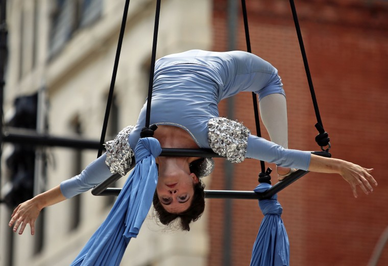 "Jesse Delaplaine, an aerialist with Daydreams + Nightmares Aerial Theatre, performs ""Brothers Avienne"" above Charles Street in the Aerial Arts Arena at Artscape 2014. (Al Drago/Baltimore Sun)"