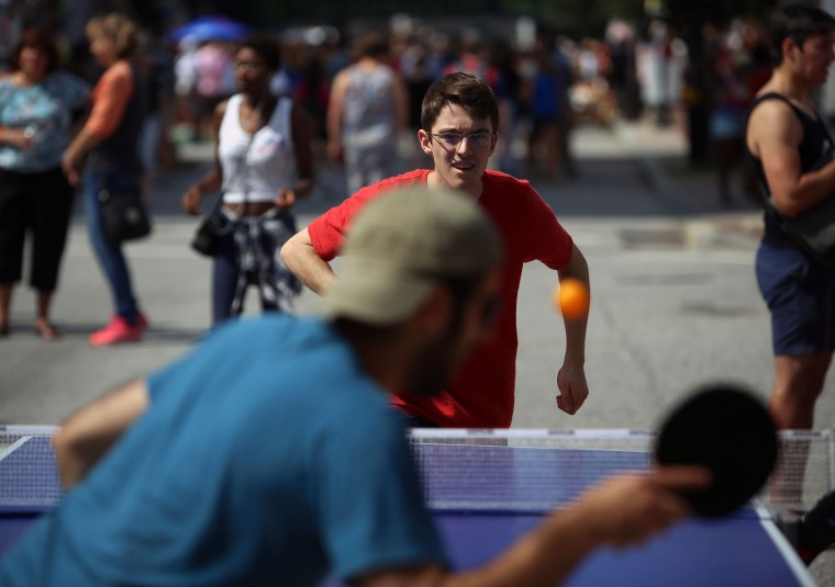 Dean Scott returns a serve to Alex Nastetsky as they play ping pong on Charles Street during Artscape 2014. Nastetsky defeated Scott 11-9. (Al Drago/Baltimore Sun)