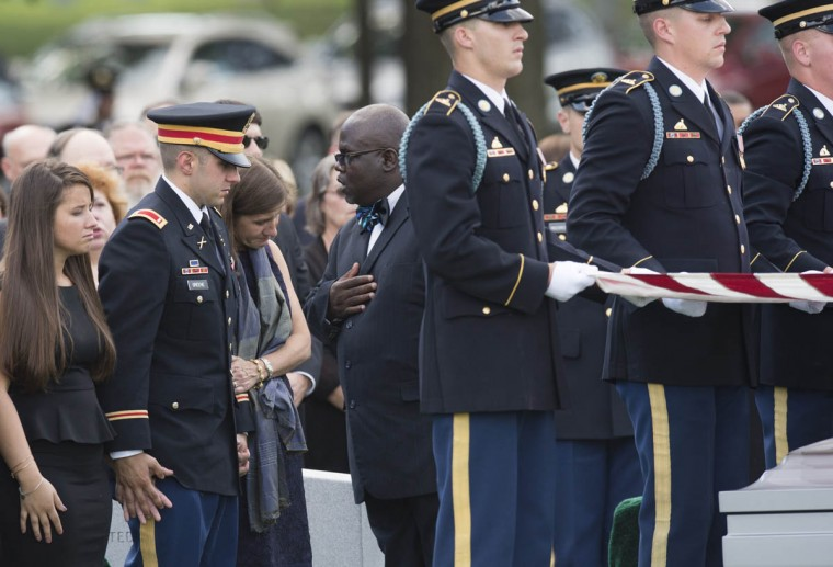 Susan Myers, widow of US Army Major General Harold J. Greene, stands alongside son First Lt. Matthew Greene (second, from left) and daughter Amelia Greene (Left) during funeral services at Arlington National Cemetery in Arlington, Virginia, on August 14, 2014. Major General Greene was shot dead on August 5, 2014 at a training center in Kabul in an attack that left more than a dozen others wounded, including a senior German officer. He was the highest ranking US Army officer killed in combat since the Vietnam War. (Saul Loeb/Getty Images)