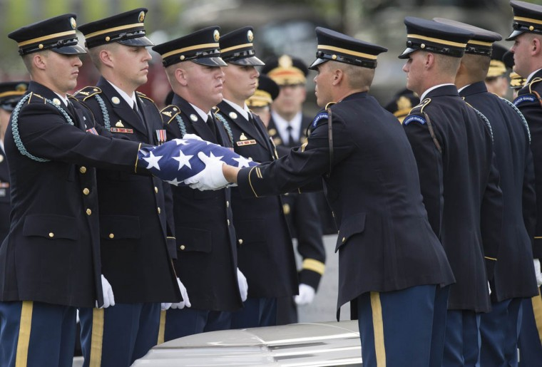Members of the Army's Old Guard fold an US flag that was draped on the casket of US Army Major General Harold Greene, during funeral services at Arlington National Cemetery in Arlington, Virginia, on August 14, 2014. Major General Harold J. Greene was shot dead on August 5, 2014 at a training center in Kabul in an attack that left more than a dozen others wounded, including a senior German officer. He was the highest ranking US Army officer killed in combat since the Vietnam War. (Saul Loeb/Getty Images)