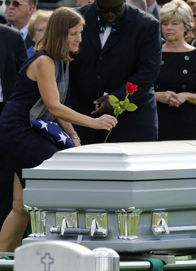 Susan Myers, wife of U.S. Army Maj. Gen. Harold J. Greene, puts a rose on his casket during the end of a full military honors funeral at Arlington National Cemetery in Virginia, August 14, 2014. Greene was killed in Afghanistan earlier this month and is the highest ranking U.S. military officer killed in combat since the Vietnam War. (Larry Downing/Reuters photo)