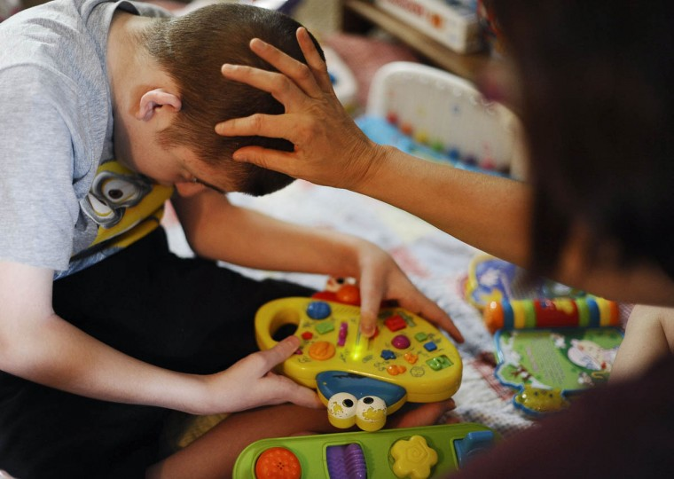 Mick Smith, 12, on left, plays with toys while his mom Cathy Smith touches his head. Mick has an undiagnosed neuromuscular disease. (Rachel Woolf/Baltimore Sun)