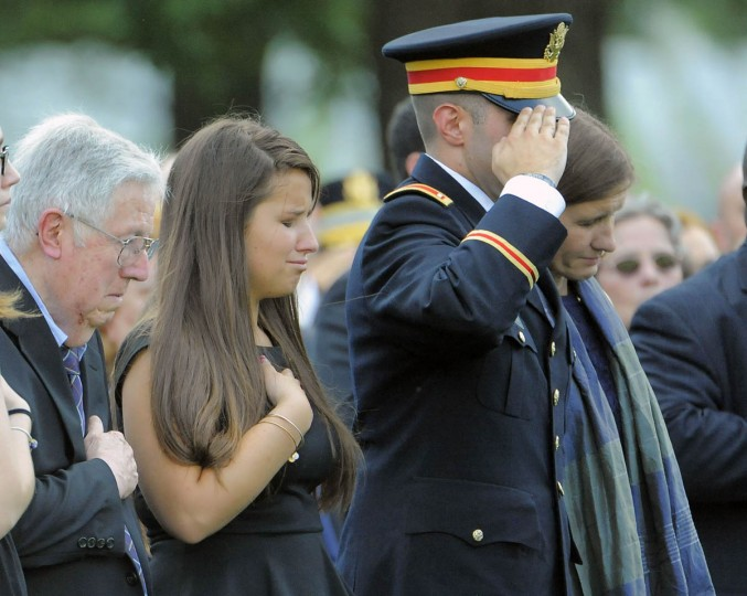 Amelia Greene, daughter of Major General Harold J. Greene of the U.S. Army, looks down as her father is honored at his burial at Arlington National Cemetery in Arlington, Va. on Thursday, August 14, 2014. Amelia is standing next to her grandfather, Harold Greene, left, 1st Lt. Matthew Greene, right, and her mother, Dr. Susan Myers, far right. (Al Drago/Baltimore Sun)