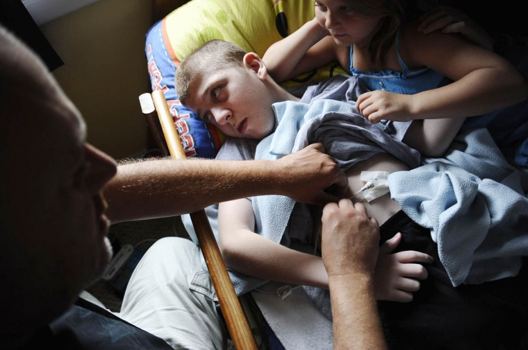 Michael Smith Jr., from left, fixes his son Mick Smith's gastric feeding tube, while he lies in bed with his sister, Martie Smith, 7. Mick has an undiagnosed neuromuscular disease. (Rachel Woolf/Baltimore Sun)