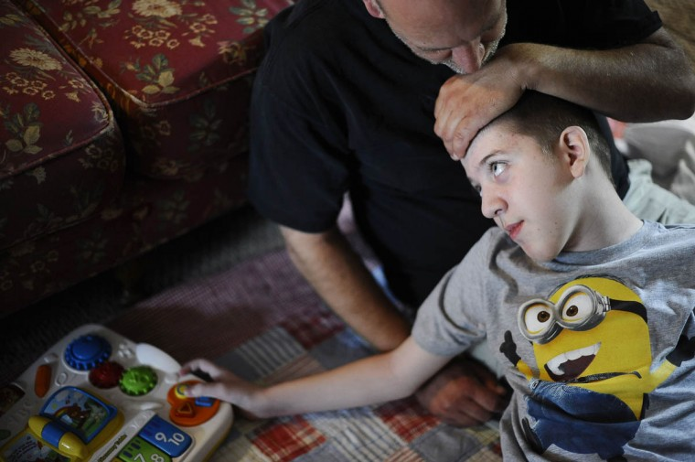 Michael Smith Jr., from left, kisses his son, Mick Smith's head. Mick, 12, has an undiagnosed neuromuscular disease. (Rachel Woolf/Baltimore Sun)
