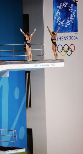 Cassandra Cardinal and Sara Hildebrand of the USA competes in the women's synchronized diving 10 metre platform event on August 16, 2004 during the Athens 2004 Summer Olympic Games at the Aquatic Centre Indoor Pool at the Olympic Sports Complex in Athens, Greece. ( Jamie Squire/Getty Images)