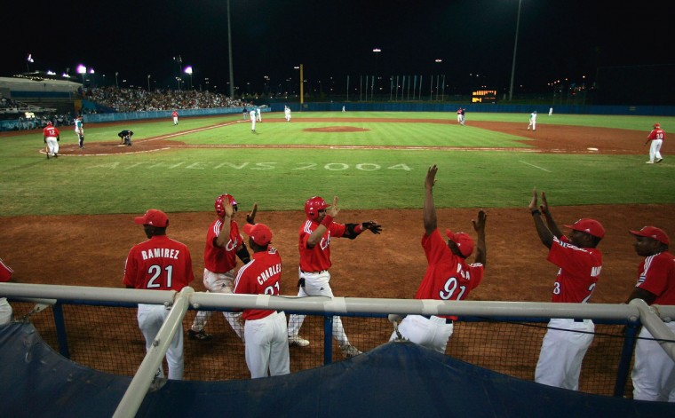 The Cuba bench celebrates as two runs score against Australia in the gold medal baseball game on August 25, 2004 during the Athens 2004 Summer Olympic Games at the Baseball Centre in the Helliniko Olympic Complex in Athens, Greece. (Donald Miralle/Getty Images)