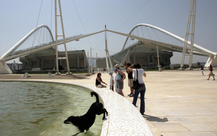 A dog jumps to a fountain in front of the Olympic stadium in Athens to cool itself as temperatures rose to 39 degrees in the city, 13 August 2005. Hundreds of tourists, children and adults visited the main Athens Olympic complex to take part in activities to celebrate the the Games' first birthday anniversary (Louisa Gouliamaki /Getty Images)