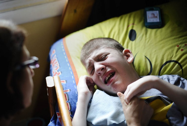 Cathy Smith, on left, holds her son, Mick Smith's hand, while he lies in bed crying. Mick has an undiagnosed neuromuscular disease. (Rachel Woolf/Baltimore Sun)