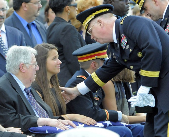 Amelia Greene, daughter of Major General Harold J. Greene of the U.S. Army, is consoled as she sits beside her grandfather, Harold Greene, left, and her brother, 1st Lt. Matthew Greene, at the burial of her father at Arlington National Cemetery in Arlington, Va. on Thursday, August 14, 2014. (Al Drago/Baltimore Sun)