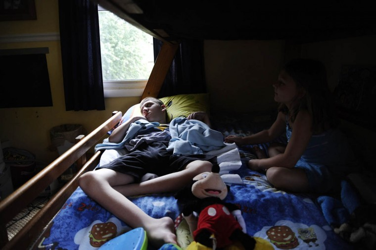 Mick Smith, 12, on left, lies in bed with his sister, Martie Smith, 7, while Mick is fed by a gastric feeding tube. Mick has an undiagnosed neuromuscular disease. (Rachel Woolf/Baltimore Sun)