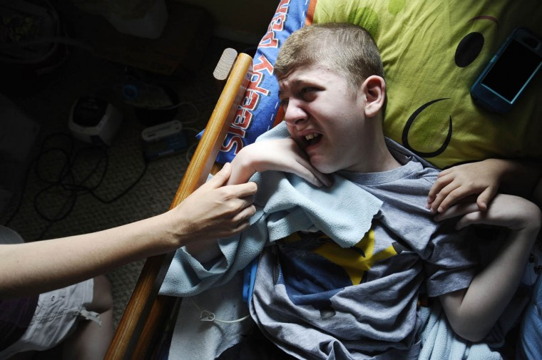 Cathy Smith, holds her son, Mick Smith's hand, while he lies in bed crying. Mick, 12, has an undiagnosed neuromuscular disease. (Rachel Woolf/Baltimore Sun)