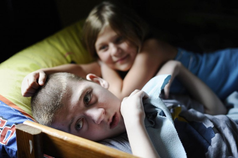 Mick Smith, 12, on left, lies in bed with his sister, Martie Smith, 7, while Mick is fed by a gastric feeding tube and while they watch TV. Mick has an undiagnosed neuromuscular disease. (Rachel Woolf/Baltimore Sun)