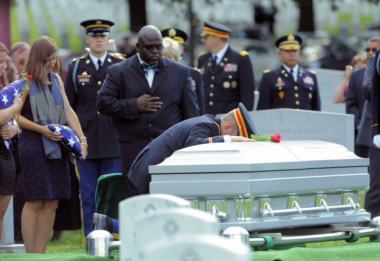 1st Lt. Matthew Greene places a rose on the casket of his father, Major General Harold J. Greene of the U.S. Army during his burial at Arlington National Cemetery in Arlington, Va. on Thursday, August 14, 2014. (Al Drago/Baltimore Sun)