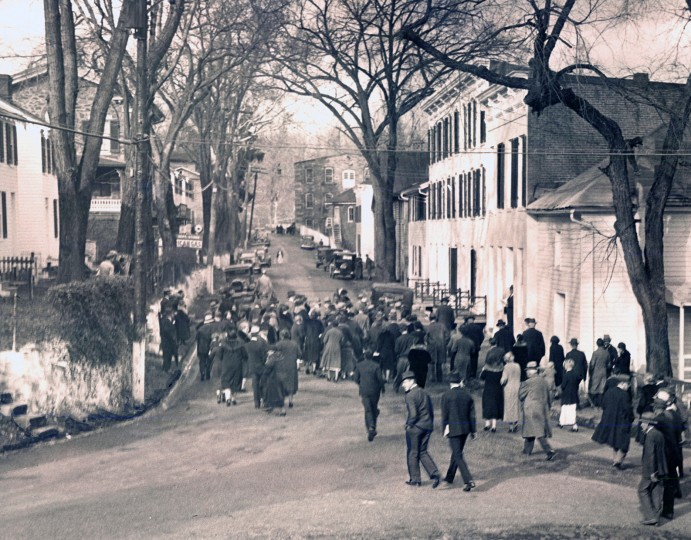 "Nov. 23, 1934: This view of the main street of Hillsdale, the mill village partly in Baltimore Co., partly Northwest Baltimore, which formerly was known as Dickeyville shows part of the crowd that turned out when the hammer of the auctioneer rang and the community was put up for mortgage sale. Practically all of the townspeople witnessed the sale. the entire village and its 60 acres were sold at auction for $42,000 to a development company that began restoring the homes to create ""an ensemble effect,"" according to a neighborhood history.(Sun file)"