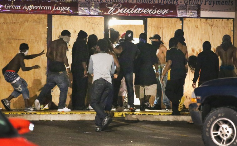 People loot the Ferguson Market and Liquor store on August 16, 2014 in Ferguson, Missouri. Several businesses were looted as police held their position nearby. Violent outbreaks have taken place almost daily in Ferguson since the shooting of Michael Brown by a Ferguson police officer on August 9. (Photo by Scott Olson/Getty Images)