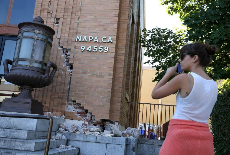 A passerby stops to take a picture of damage to the Napa post office following a reported 6.0 earthquake on August 24, 2014 in Napa, California. A 6.0 earthquake rocked the San Francisco Bay Area shortly after 3:00 am on Sunday morning causing damage to buildings and sending at least 70 people to a hospital with non-life threatening injuries. (Justin Sullivan/Getty Images)