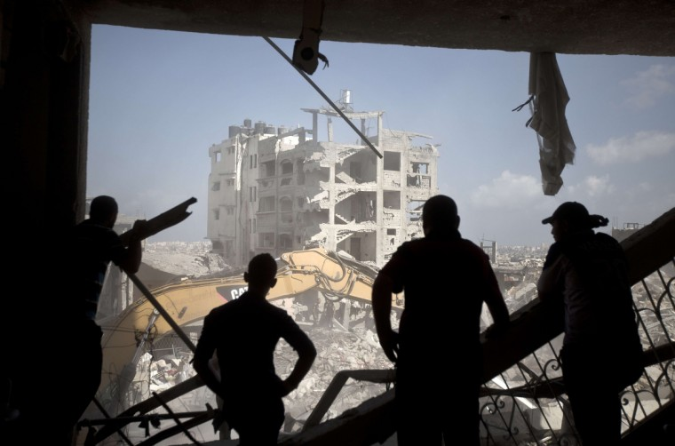 Palestinian men inspect destruction in part of Gaza City's al-Tufah neighborhood as the fragile ceasefire in the Gaza Strip entered a second day on August 6, 2014 while Israeli and Palestinian delegations prepared for crunch talks in Cairo to try to extend the 72-hour truce. The ceasefire, which came into effect on August 5, has brought relief to both sides after one month of fighting killed 1,875 Palestinians and 67 people on the Israeli side. (Mahmud Hams/Getty Images)