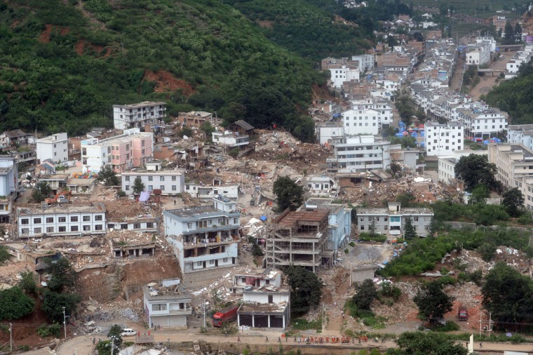 A team of rescuers (bottom) walk in a disaster-hit town in Ludian county in Zhaotong, southwest China's Yunnan province. The death toll from an earthquake that devastated a remote region of China jumped to nearly 600 people, authorities said, as volunteer rescuers were warned away. (Getty Images)