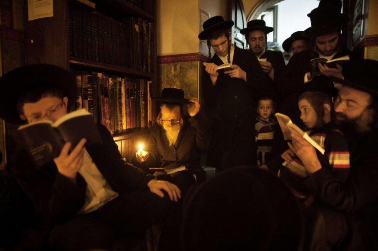 Ultra-Orthodox Jewish men use a candle light to read from the book of Eicha (Book of Lamentations) during the annual Tisha BAv (Ninth of Av) fasting and a memorial day, commemorating the destruction of ancient Jerusalem temples, in the Ultra-Orthodox neighborhood of Mea Shearim in Jerusalem. Religious Jews in Israel and around the world began traditional prayers and fasting today to commemorate the destruction of the First and Second holy temples in Jerusalem. Commemorated under the Hebrew calendar as the Ninth of Av, worshippers will gather all night long at the Wailing Wall, the last remaining vestige of the Second Temple, in Jerusalem Old City. (Menahem Kahana/Getty Images)