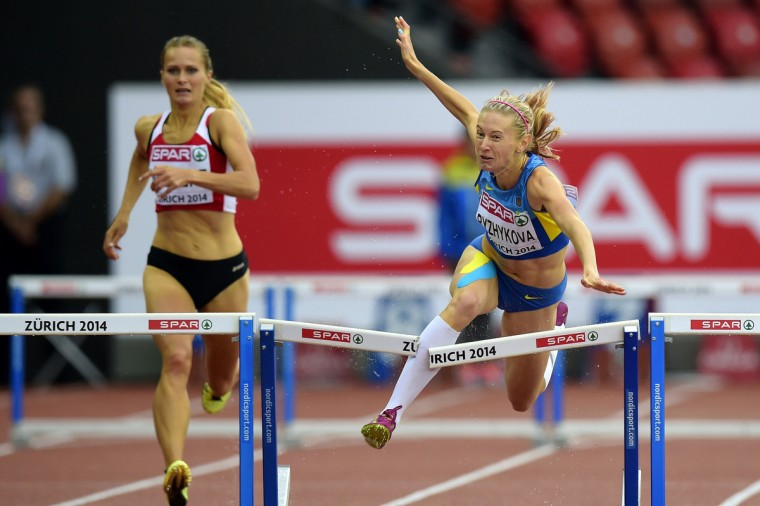 Ukraine's Hanna Ryzhykova (R) crashes out in the women's 400m hurdles heats during the European Athletics Championships at the Letzigrund stadium in Zurich. (Olivier Morin/Getty Images)