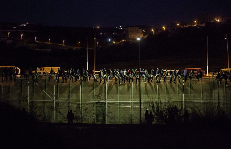 Spanish Guardia Civil watch as would be immigrants from Africa sit atop a wire-meche fence after scrambling over two other border barriers on Spain's tiny north African territory of Melilla. Some 600 people tried to scale the triple-layer six-metre-high (20-foot) razor-wire barrier that separates Morocco from Melilla in a pre-dawn assault today, said Irene Flores, spokeswoman for the Spanish government in Melilla. More than 60 of them had perched on the top of the border fence, she told AFP. (Jose Colon/Getty Images)