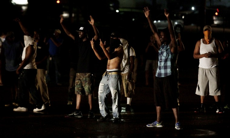Demonstrators taunt police officers on August 15, 2014, during a protest against the shooting death of 18-year-old Michael Brown in Ferguson, Missouri. Vandals attacked stores in Ferguson early August 16, hours after police said the unarmed black teenager shot dead by a white officer in an incident that unleashed days of rioting was a robbery suspect. The allegation reignited anger in the town, a St. Louis suburb in the state of Missouri that has endured on-and-off rioting since 18-year-old Michael Brown was killed on August 9. (Joshua Lott/AFP/Getty Images