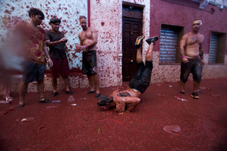 "Revelllers dance during the annual ""tomatina"" festivities in the village of Bunol, near Valencia. Some 22,000 revellers hurled 130 tons of squashed tomatoes at each other drenching the streets in red in a gigantic Spanish food fight known as the Tomatina. (Gabriel Gallo/Getty Images)"