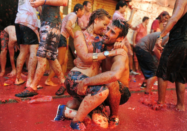 Revellers cuddle in tomato pulp during La Tomatina festival, the world's biggest tomato fight on August 25, 2010 in Bunol, Spain. More than 45000 people from all over the world descended on the small Valencian town to participate in this year's La Tomatina festival, with the local town hall estimating that over 100 tons of rotten and over-ripe tomatoes were thrown. (Photo by Jasper Juinen/Getty Images)