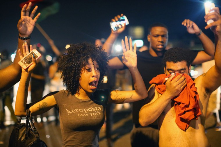 Demonstrators protesting the killing of teenager Michael Brown by a Ferguson police officer try to stand their ground despite being overcome by tear gas on August 17, 2014 in Ferguson, Missouri. Despite the Brown family's continued call for peaceful demonstrations, violent protests have erupted nearly every night in Ferguson since his death. (Scott Olson/Getty Images)