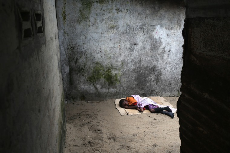 A very sick Saah Exco, 10, lies in a back alley of the West Point slum on August 19, 2014 in Monrovia, Liberia. The boy was one of the patients that was pulled out of a holding center for suspected Ebola patients when the facility was overrun by a mob on Saturday. A local clinic Tuesday refused to treat the boy, according to residents, because of the danger of infection. The virus has killed more than 1,000 people in four African nations, more in Liberia than any other country. (Photo by John Moore/Getty Images)