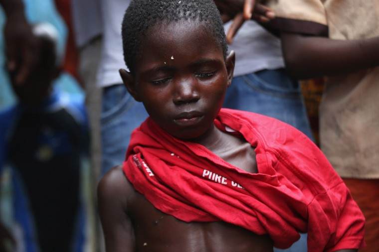 Local residents dress a sick Saah Exco, 10, after bathing him in a back alley of the West Point slum on August 19, 2014 in Monrovia, Liberia. According to communitey organizer John Saah Mbayoh, Saah's mother died of suspected but untested Ebola in West Point before he was brought to the isolation center the evening of August 13. He came with his brother, Tamba, 6, aunt Ma Hawa, and cousins. His brother died on August 15 at the center. Saah fled the center the August 15 with several other patients before it was overrun on August 16 by a mob. Once out in the neighborhood, he was not sheltered, as he had suspected Ebola - so he has been sleeping outside. Residents reportedly began giving him medication, a drip and oral rehydration liquids today. The whereabouts and condition of his aunt and cousins, who left the facility when it was overran by the crowd, is still unknown at this time. The Ebola virus has killed more than 1,000 people in four African nations, more in Liberia than any other country. (Photo by John Moore/Getty Images)