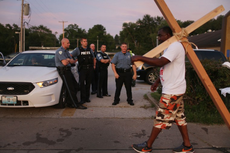 Police watch as peaceful demonstrators continue protesting the shooting death of Michael Brown August 23, 2014 in Ferguson, Missouri. Protesters have been vocal asking for justice in the shooting death of Michael Brown by a Ferguson police officer on August 9th. (Joe Raedle/Getty Images)