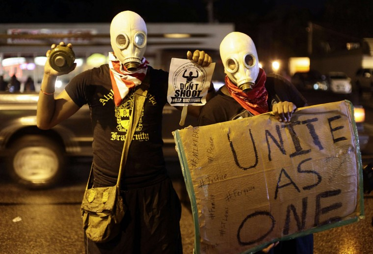Masked demonstrators protest against the August 9 police shooting of 18-year-old Michael Brown by holding up signs on the streets of Ferguson, Missouri late on August 16, 2014. A crowd of some 200 demonstrators defied a curfew that came into effect in Ferguson early on August 17, days after police shot dead the unarmed black teen, triggering a wave of rioting. (Joshua Lott/AFP/Getty Images)