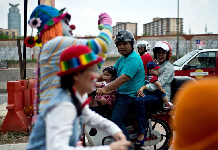 A Malaysian family watches as clowns take part in a parade during the Clown Festival in Kuala Lumpur on August 17, 2014. Around 80 clowns from all over Malaysia took part in the event organized by the Association of Clowns Malaysia to provide a platform for clown education, acquiring new skills and offering members support. (Manan Vatsyayana/AFP/Getty Images)