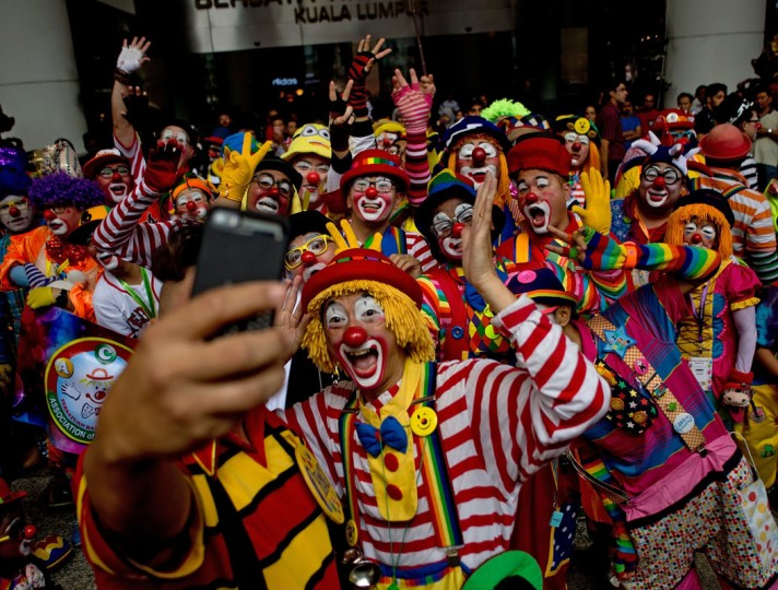Clowns pose for a selfie after a parade during the Clown Festival in Kuala Lumpur on August 17, 2014. Around 80 clowns from all over Malaysia took part in the event organized by the Association of Clowns Malaysia to provide a platform for clown education, acquiring new skills and offering members support. (Manan Vatsyayana/AFP/Getty Images)