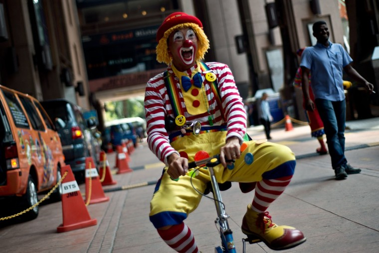 Malaysian clown Sam Tee, aka Uncle Button, rides a bicycle at a parade during the Clown Festival in Kuala Lumpur on August 17, 2014. Around 80 clowns from all over Malaysia took part in the event organized by the Association of Clowns Malaysia to provide a platform for clown education, acquiring new skills and offering members support. (Manan Vatsyayana/AFP/Getty Images)