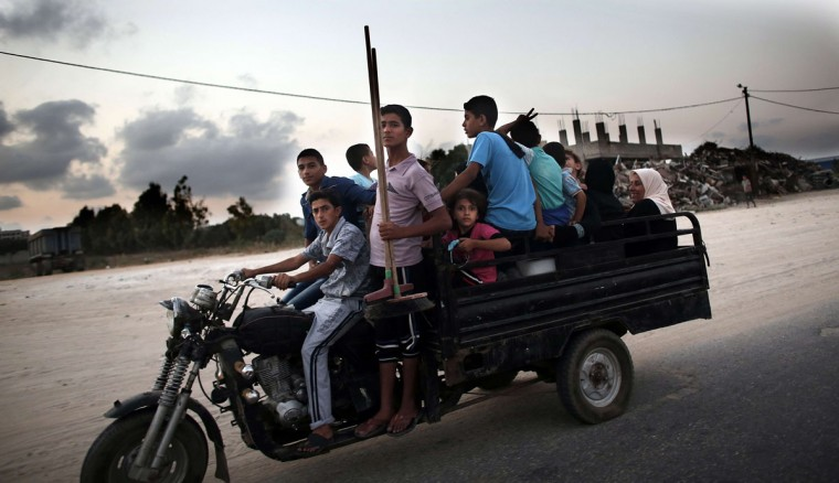 Palestinians flee their destroyed neighbourhood to head to a United Nations school to take refuge for the night in the northern Gaza Strip city of Beit Hanun, on August 18, 2014. Prime Minister Benjamin Netanyahu warned that Israel will hit back hard if Palestinian rocket attacks from Gaza resume, speaking just hours before the midnight expiry of a five-day ceasefire. (AFP PHOTO/Getty Images/Thomas Coex)
