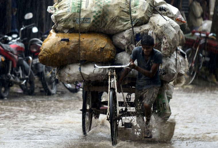 A Bangladeshi rickshaw puller makes his way through the rain in Dhaka on August 19, 2014. Seven rivers in Bangladesh are flowing above the danger mark after heavy rains. (AFP PHOTO/Getty Images/Munir uz Zaman)