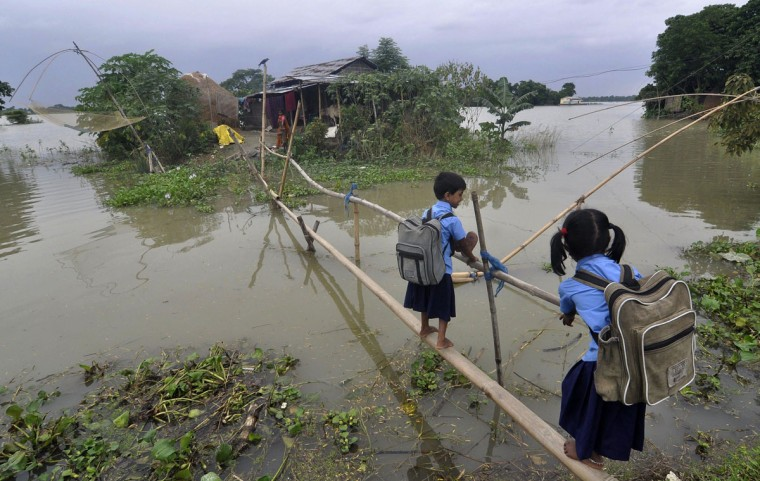 Indian schoolchildren use a bamboo bridge to cross floodwaters in Morkata village in the Morigoan district of Assam on August 25, 2014. Floods and landslides in Nepal and India have killed nearly 200 people and scores more are missing. (BIJU BORO/AFP/Getty Images)